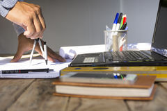 Man architect using circus for project plan with equipment on white table.Zoom in and beside. Royalty Free Stock Photos