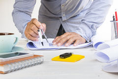 Man architect using circus for project plan with equipment on white table. Zoom in Royalty Free Stock Photo