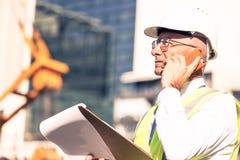 Man architector outdoor at construction area having mobile conve Stock Photos
