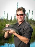 Man with Arctic Grayling Fish Royalty Free Stock Photo