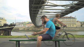 Man arguing by the cellphone, sitting with laptop on the bench. stock video footage