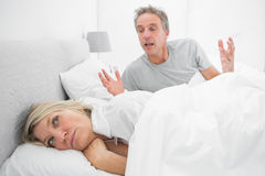 Man arguing with his partner in bed Stock Photography