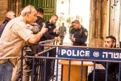 A man arguing with Israeli policeman. Jerusalem, Israel - November 3, 2015: A man arguing with Israeli policeman next to gate leading to Temple Mount royalty free stock photo