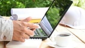 Man arkitekten som dricker kaffe och den använda smartphonen i hans hand och, projektera planet med utrustning på den vita tabell stock video