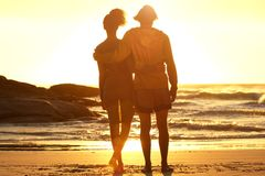 Man with arm around woman standing at the beach Stock Photo