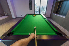 Man arm playing Snooker Pool green table in a modern games room. Man& x27;s arm playing pool about to break and start the game shooting the white ball to the Royalty Free Stock Photo