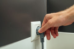 Man arm put jack into plug in the room Royalty Free Stock Image