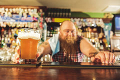 Man arm putting alcohol beverage in alehouse Stock Photography
