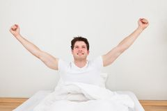 Man with arm raised on bed Royalty Free Stock Photo