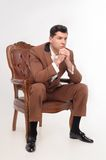 Man in armchair. Young attractive serious man in brown suit sitting in armchair isolated on white background Royalty Free Stock Photography
