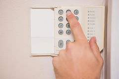 Man arming a home alarm. On the wall Royalty Free Stock Image