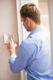 Man arming a home alarm. On the wall Royalty Free Stock Photography