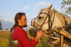 Man in an armor and white horse Stock Photography