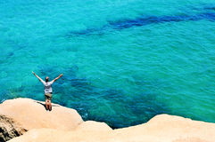 Man with the arms in the air in front of the ocean. A young man with the arms in the air in front of the ocean, feeling free Stock Photo