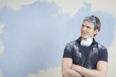 Man With Arms Crossed Against Incomplete Painted Wall. Thoughtful young man with arms crossed against incomplete painted wall stock image