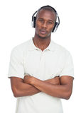 Man with arms crossed listening to music Stock Image