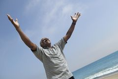 Man with arms outstretched at beach Stock Photography