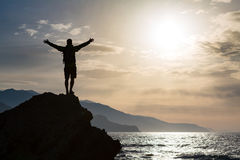 Man with arms outstretched celebrate mountains sunrise. Man with arms outstretched celebrating or praying in beautiful inspiring sunrise with mountains and sea stock photos