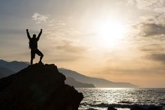 Man with arms outstretched celebrate mountains sunrise. Man with arms outstretched celebrating or praying in beautiful inspiring sunrise with mountains and sea stock images