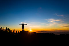 Man with arms outstretched celebrate mountains sunset Stock Images