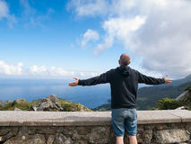 Man with arms outstretched in front of a coastal landscape Stock Photography