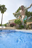 Man with arms outstretched jumping into swimming pool.  stock photos