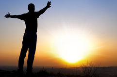 Man arms outstretched to the side at sunset Stock Images