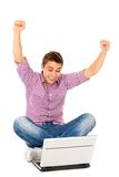 Man with arms raised sitting with laptop Stock Image