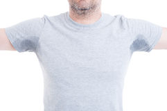 Man with arms raised and sweat stains. Man with both arms raised and excessive sweat stains on grey t-shirt isolated on white as hyperhidrosis concept royalty free stock images