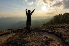 Man with arms raised on the top of a rock Stock Photography