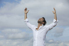 Man with arms raised under cloudy sky. Man eyes closed with arms raised under cloudy sky Royalty Free Stock Photography