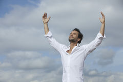 Man with arms raised under cloudy sky. Man pacefull  with arms raised under cloudy sky Stock Photography