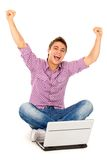 Man with arms raised using laptop. Young man sitting with laptop Royalty Free Stock Images