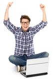 Man with arms raised using laptop. Young man sitting on floor with laptop Stock Images