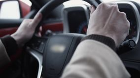 Man arms on steering wheel driving expensive automobile on bright day. Futuristic dashboard, close up stock footage