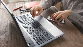 Man arms typing on keyboard at natural hardwood desk. With green flora background many electronic gadgets dropped around tablet PC smart phone color pencils stock footage