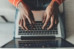 Man arms using laptop with comfort. Top view close up of hands of young male person touching notebook clavier while resting on couch stock image