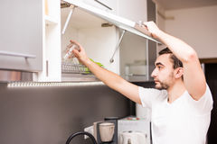 Man arrange washing dishes in kitchen at home Stock Photography