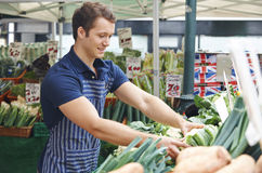 Man Arranging Display On Market Vegetable Stall Stock Images