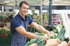 Man Arranging Display On Market Vegetable Stall Royalty Free Stock Photo