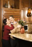Man arranging flowers while being kissed. Caucasian woman kissing Caucasian man on cheek as he arranges flowers in vase in kitchen Royalty Free Stock Image