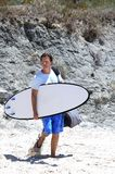 Man arriving at the beach to surf stock photo
