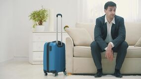 Man arriving at hotel room with suitcase and sits on the sofa looking very tired.