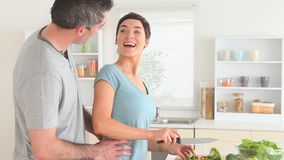 Man arriving while woman prepares dinner stock video footage