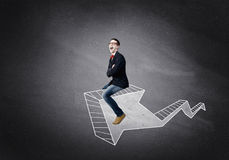 Man on arrow graph. Young businessman riding drawn graph arrow going up Royalty Free Stock Photo