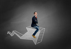 Man on arrow graph. Young businessman riding drawn graph arrow going up Royalty Free Stock Photography