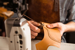 Man artisan sewing leather shoes indoors. At a workshop royalty free stock image