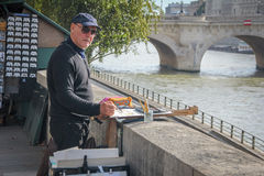 A man artist painting by the seine river Stock Image