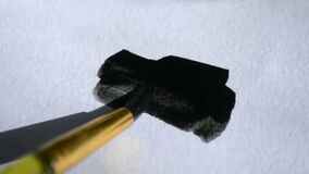 Man artist paints with brush strokes of black paint watercolor