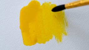 Man artist paints with brush strokes of yellow paint watercolor